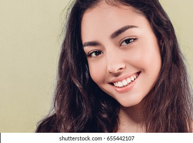 Beauty Woman with perfect healthy skin Portrait. Beautiful Girl smiling Spa model, pampering her skin. Yellow background