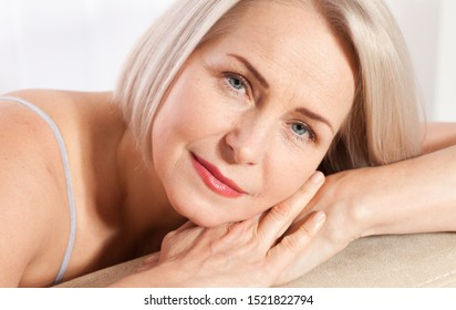 Beauty Woman with perfect skin Portrait. Beautiful middle aged blonde woman shows off her perfectly well-groomed face. Plastic surgery and collagen injections. Macro face. Selective focus on face.