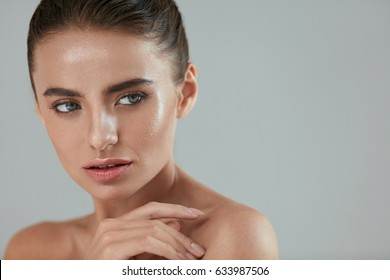 Beauty Woman Portrait. Beautiful Sexy Girl Touching Smooth Fresh Glowing Skin On Grey Background. Young Female Model With Highlighting Makeup And Highlighter On Face And Body Skin. High Resolution