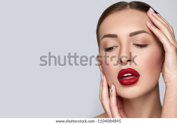 Beauty Woman Portrait with clean skin and red lips. Professional Makeup for Brunette. Beautiful Fashion Model Girl. Perfect Skin Contouring Make up. Grey Background, horizontal
