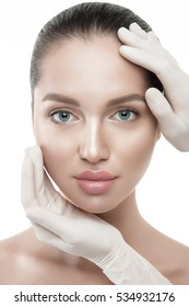 Beauty woman portrait close up on white background with hands in medical gloves on face.