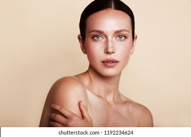 Beauty woman portrait with nude makeup shooted on a beige background