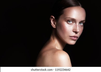 Beauty woman portrait with nude makeup shooted on a black background