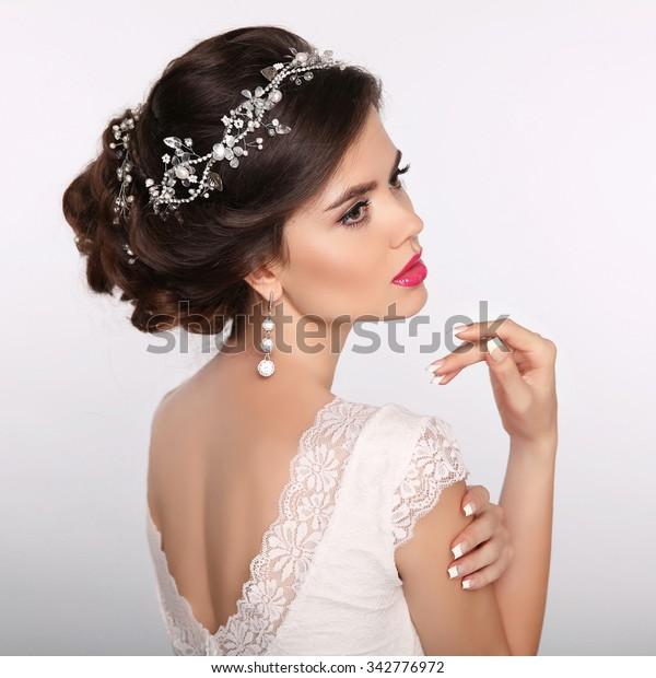 Schönheit Frauenporträt. Hochzeitsfrisur. Wunderschönes Modell für Brautjunges. Luxusschmuck. Manikulierte Nägel. Attraktive junge Frau mit Frisur.