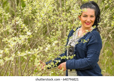 Beauty woman posing in nature with young leaf of tree