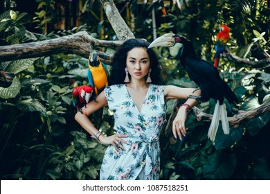 Beauty woman posing with parrot, Portrait of young attractive woman in african style with ara parrot on her hand on colorful background, fashion model, nature, park, birds