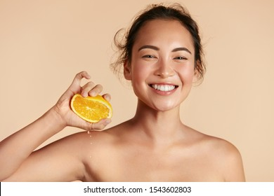 Beauty. Woman with radiant face skin squeezing orange in hand portrait. Beautiful smiling asian girl model with natural makeup, glowing facial skin and citrus fruit. Vitamin C cosmetics concept - Shutterstock ID 1543602803