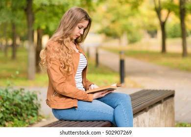 Beauty woman reading a book in the park an autumn day