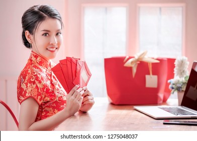 beauty woman in red dress traditional cheongsam holding red envelopes and using laptop shopping online for chinese new year