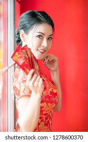 Beauty woman in red dress traditional cheongsam holding red envelopes in chinese new year