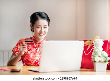 Beauty woman in red dress traditional cheongsam holding red credit card shopping online for chinese new year.