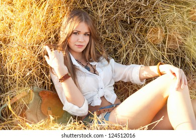 Beauty woman relaxing in the straw in field. Young woman in costume of cowboy looks at camera.