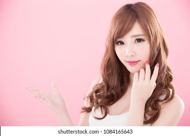 beauty woman show something to you on the pink background