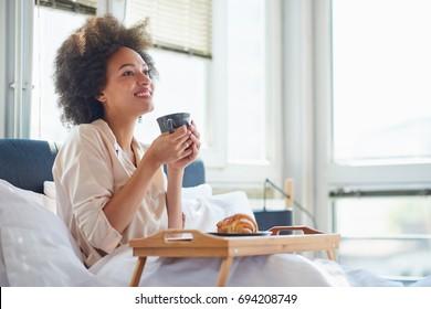 Beauty woman sitting on bed, eating breakfast
