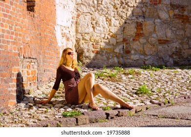 Beauty woman sitting under the sunlight in a sunglasses