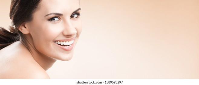 Beauty woman, skin or dental care concept face portrait. Beautiful girl with perfect clean skin. Brunette female model. Blank copy space area for some advertising text or slogan. Beige background.