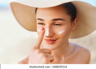 Beauty Woman smile applying sun cream on face. Skincare. Body Sun protection. sunscreen. Female in hat smear  moisturizing lotion on skin.