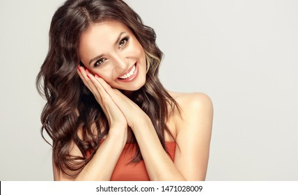 Beauty woman with smile surprise holds cheeks by hand .Beautiful girl  with curly hair laugh sincerely. Presenting your product. Expressive facial expressions . Happy people .