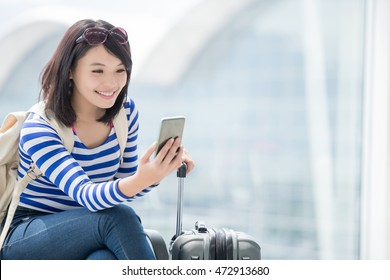 beauty woman take smart phone and smile in airport, asian