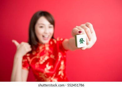 beauty woman thumb up and show mahjong to you in chinese new year - Rich and wealthy text on girl hand in Chinese words