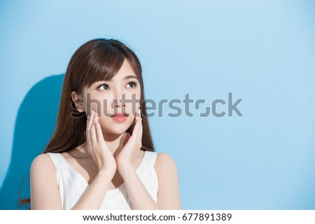 beauty woman touch her face on the blue background