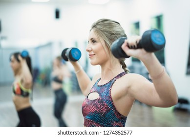 Beauty woman training in sport class with dumbbells in gym indoors smiling