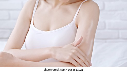 beauty woman use cream with arm at home