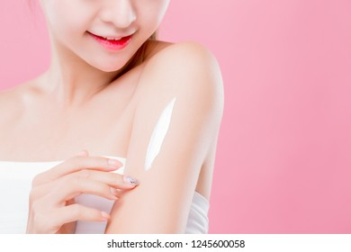 beauty woman use cream with arm isolated on pink background