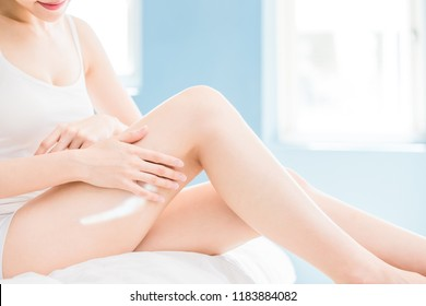beauty woman use cream with her leg at home
