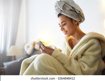 beauty woman using smartphone at home. a woman in a bathrobe and with a towel on her head sits on the sofa