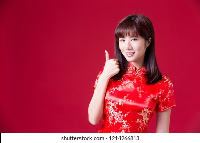 beauty woman wear cheongsam and show thumb up in chinese new year