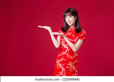 beauty woman wear cheongsam and show something in chinese new year
