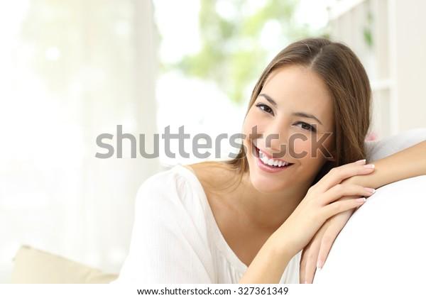 家でカメラを見ながら白く完璧な笑みを浮かべた美人