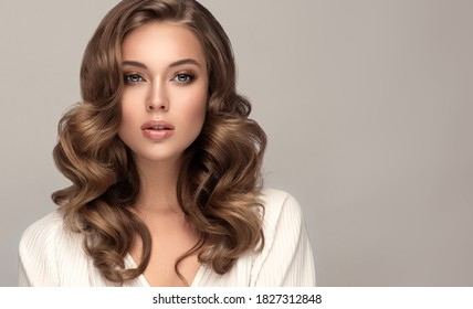 Beauty  woman in a white shirt with long  and   shiny wavy  hair .  Beautiful blonde   woman model with curly hairstyle .