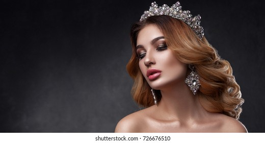 Beauty of a woman's face with a beautiful hairdo. The image of the queen. Dark long wavy hair, crown on the head, clean skin, pouting lips. Gray background with a place for inscriptions, panorama