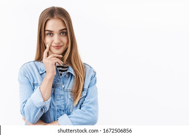 Beauty and women concept. Waist-up portrait tender, romantic blond girl in denim jacket, touching cheek and flirty smiling, look alluring with sensual dreamy gaze, standing white background