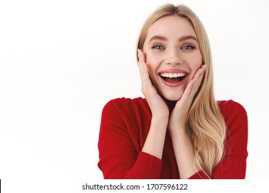 Beauty, women and fashion concept. Close-up portrait of amused, surprised blond girl receive incredible good news, touch cheeks and smiling amused, glad to win, triumphing, white background