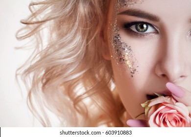 Beauty women portrait. half face of young curly blond woman with pastel manicure and perfect art make-up with glitter. Rose in her mouth .Studio