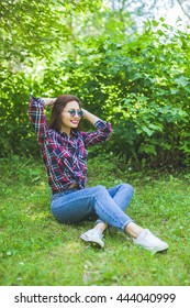 Beauty women with sunglasses sitting on grass, smiling, relaxing