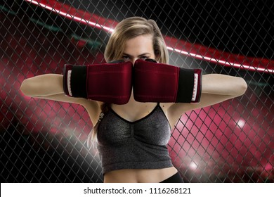 Beauty young blonde woman fighter looks at the camera in the red corner of the cage