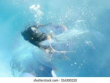 Beauty young bride in wedding dress falling underwater. Double exposure.
