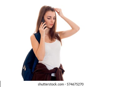 beauty young brunette student girl with backpack talking phone isolated on white background