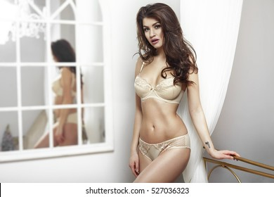 beauty young brunette woman in sexy underwear standing at the white wall and mirror