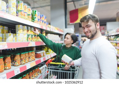 The beauty of a young couple buys canned vegetables in a supermarket. Portrait of a smiling man in a supermarket