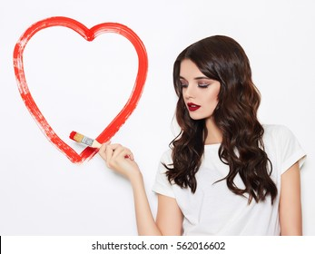 beauty young happy woman draws heart on white wall.beautiful girl.Valentine's Day