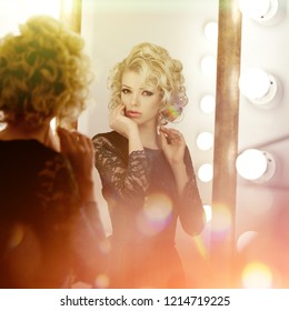 Beauty young model woman in luxurious evening dress in a fairy luxury apartment. Beautiful makeup and hairstyle. Classic vintage home interior. Light rays of a nightclub.