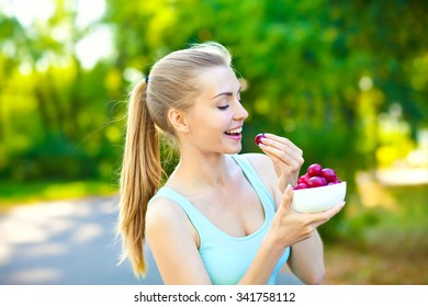Beauty young smiling woman with plate of fruits outdoors