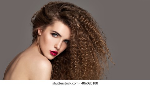 Beauty young woman with curly big and long hair. Permed hair. Glamour lady, Beauty Girl on grey background. Beautiful Woman Portrait. Blond Wavy Hair, perfect make up, pink lips, thick eyelashes.