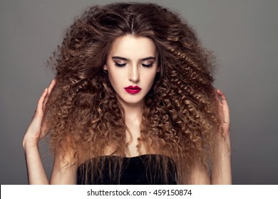 Beauty young woman with curly small and long hair. Permed hair. Glamour lady,  Beautiful Girl on gray background. Portrait. Wavy Hair, perfect make up, red lips, thick eyelashes. Closed eyes.