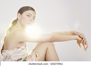 Beauty young woman with direct back light posing in a white background.